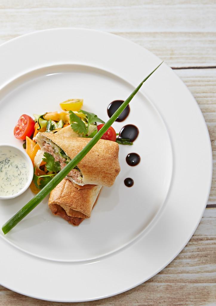 Tortilla z łososiem zapiekana z klarowanym masłem, podana na marynowanych warzywach z sosem koperkowo-szczypiorkowym